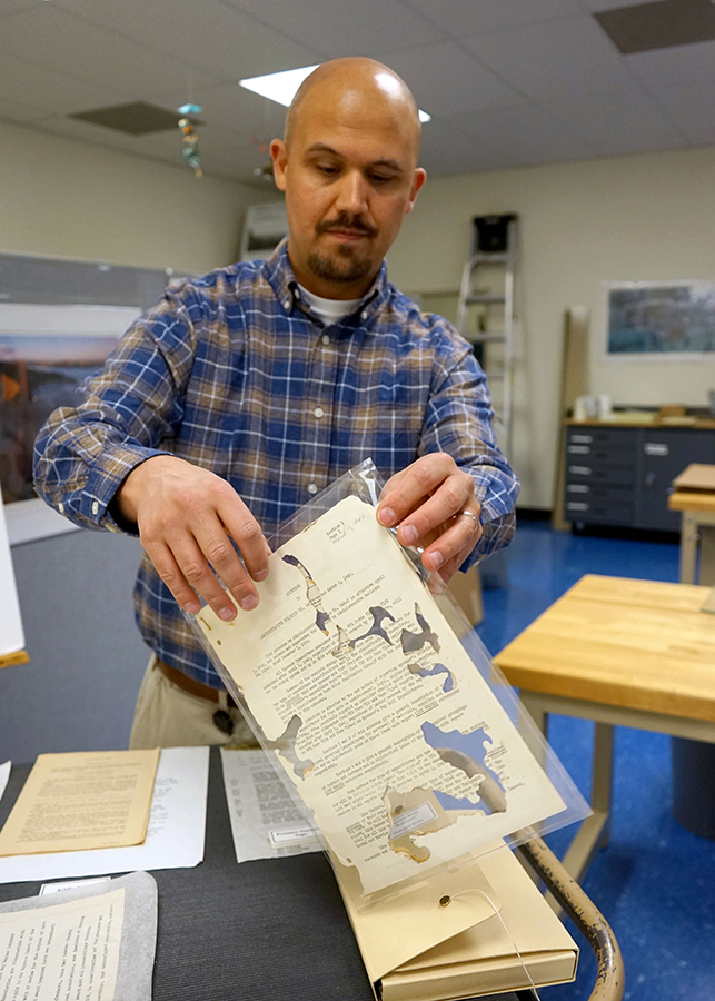 State Archives technicians, like Jackson, try to repair damaged documents sent to them.